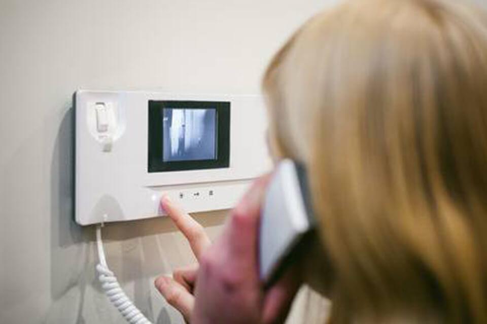 Mujer contestando el portero eléctrico con video