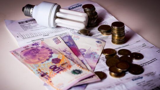 Factura de electricidad con dinero y lámpara encima